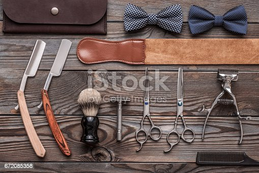 672088820 istock photo Vintage barber shop tools on wooden background 672085358