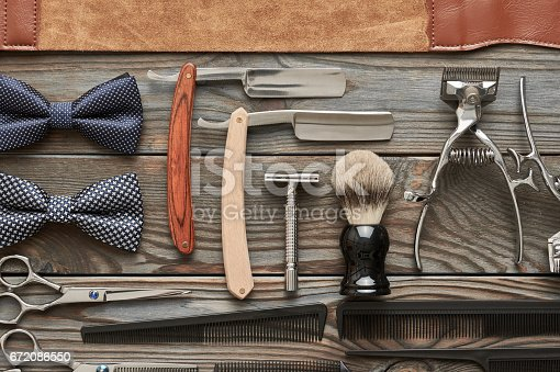 672088820 istock photo Vintage barber shop tools on wooden background 672086550