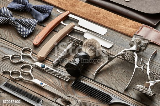 672088820 istock photo Vintage barber shop tools on wooden background 672087100