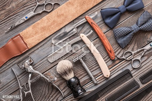 672088820 istock photo Vintage barber shop tools on wooden background 672087152