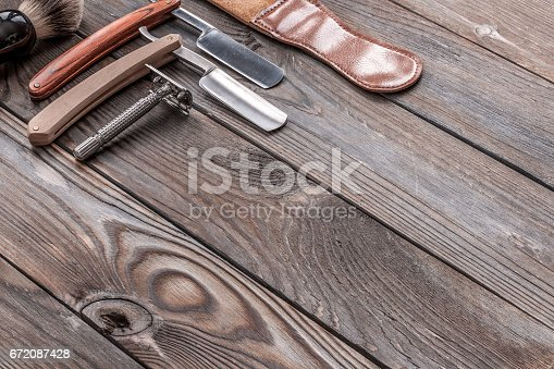 672088820 istock photo Vintage barber shop tools on wooden background 672087428