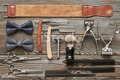 672088820 istock photo Vintage barber shop tools on wooden background 672087444