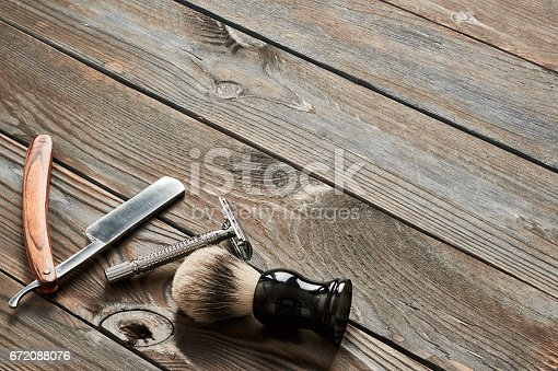 672088820 istock photo Vintage barber shop tools on wooden background 672088076
