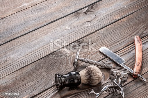 672088820 istock photo Vintage barber shop tools on wooden background 672088150