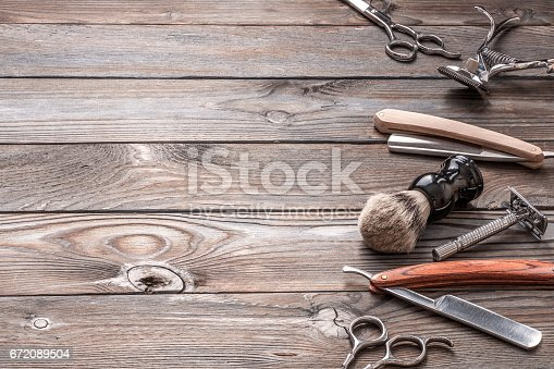 672088820 istock photo Vintage barber shop tools on wooden background 672089504