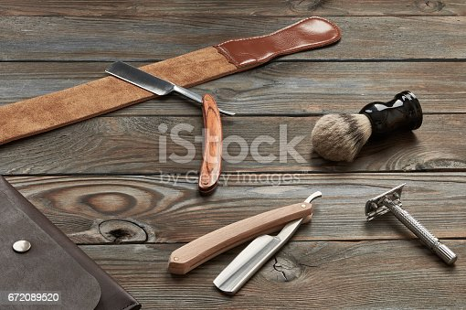 672088820 istock photo Vintage barber shop tools on wooden background 672089520