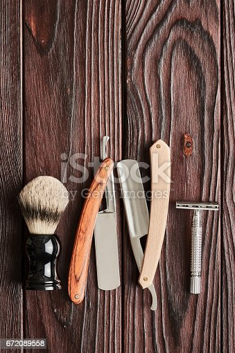 672089638 istock photo Vintage barber shop tools on wooden background 672089558