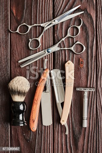 672089638 istock photo Vintage barber shop tools on wooden background 672089562