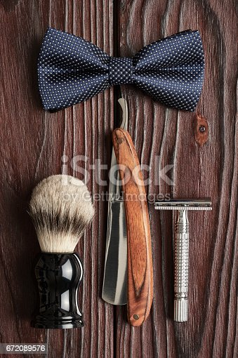 672089638 istock photo Vintage barber shop tools on wooden background 672089576