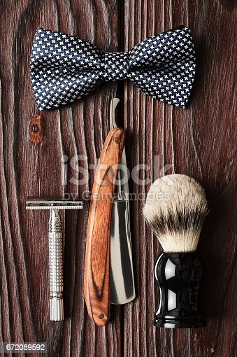 672089638 istock photo Vintage barber shop tools on wooden background 672089592