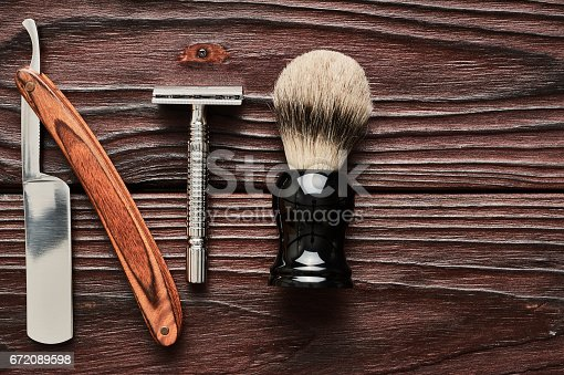 672088820 istock photo Vintage barber shop tools on wooden background 672089598
