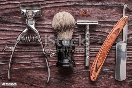 672088820 istock photo Vintage barber shop tools on wooden background 672089608