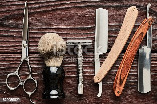 672088820 istock photo Vintage barber shop tools on wooden background 672089622