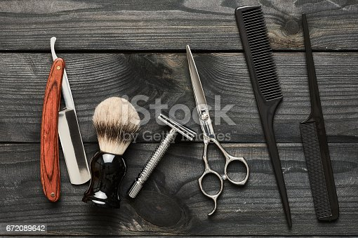 672088820 istock photo Vintage barber shop tools on wooden background 672089642