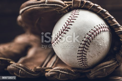 A group of vintage baseball equipment, bats, gloves, baseballs on wooden background