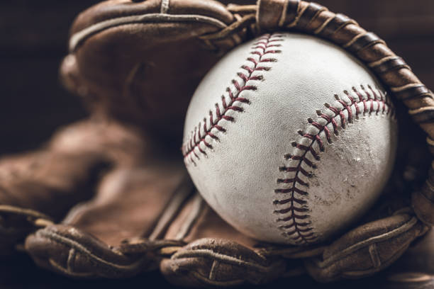 Vintage baseball gear on a wooden background A group of vintage baseball equipment, bats, gloves, baseballs on wooden background baseball sport stock pictures, royalty-free photos & images