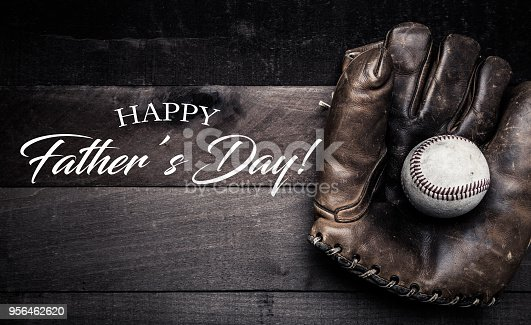 A group of vintage baseball equipment, bats, gloves, baseballs on wooden background with a father's day greeting