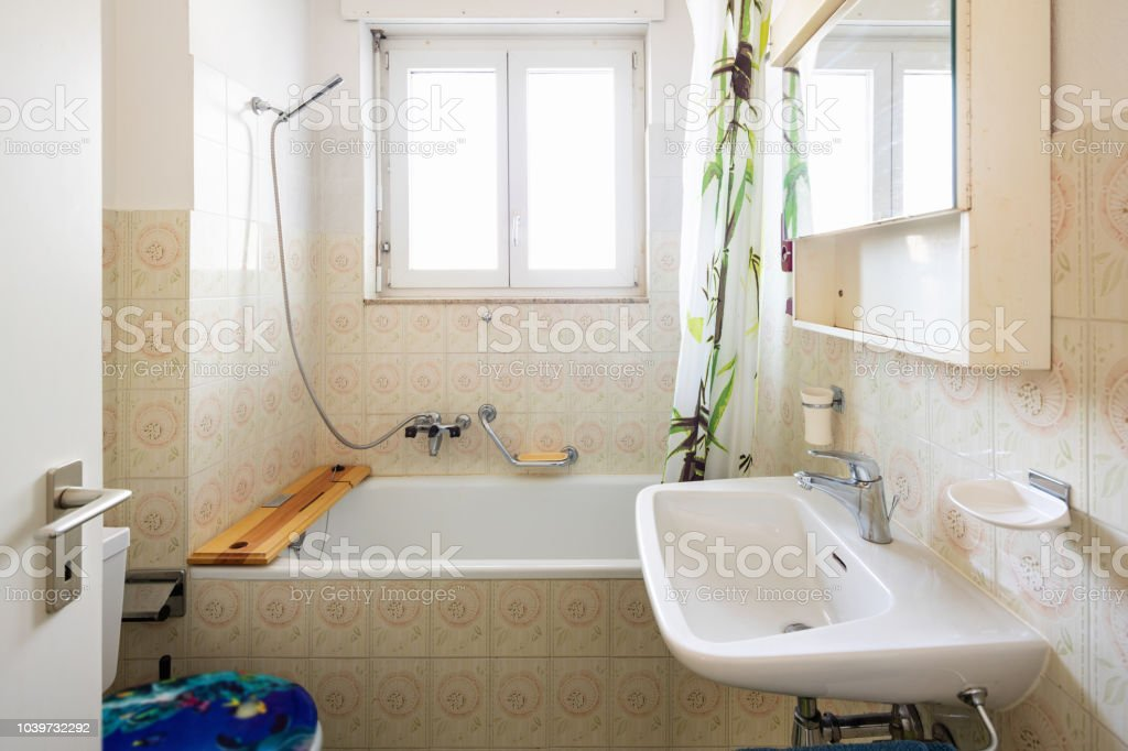 Vintage bathroom with green tiles and window stock photo