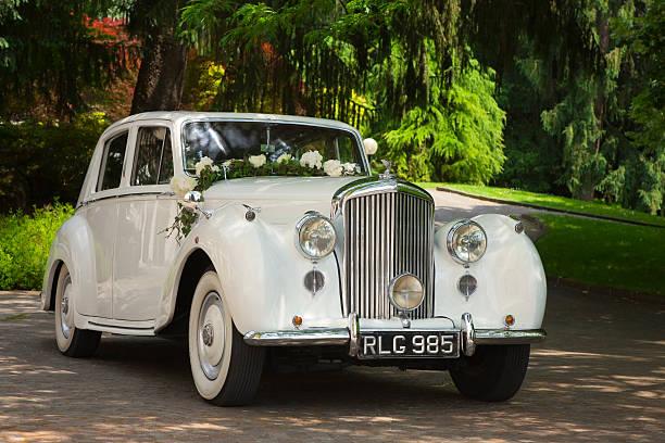 vintage bentley hochzeit auto mit blumen im park - grüne wald hochzeiten stock-fotos und bilder