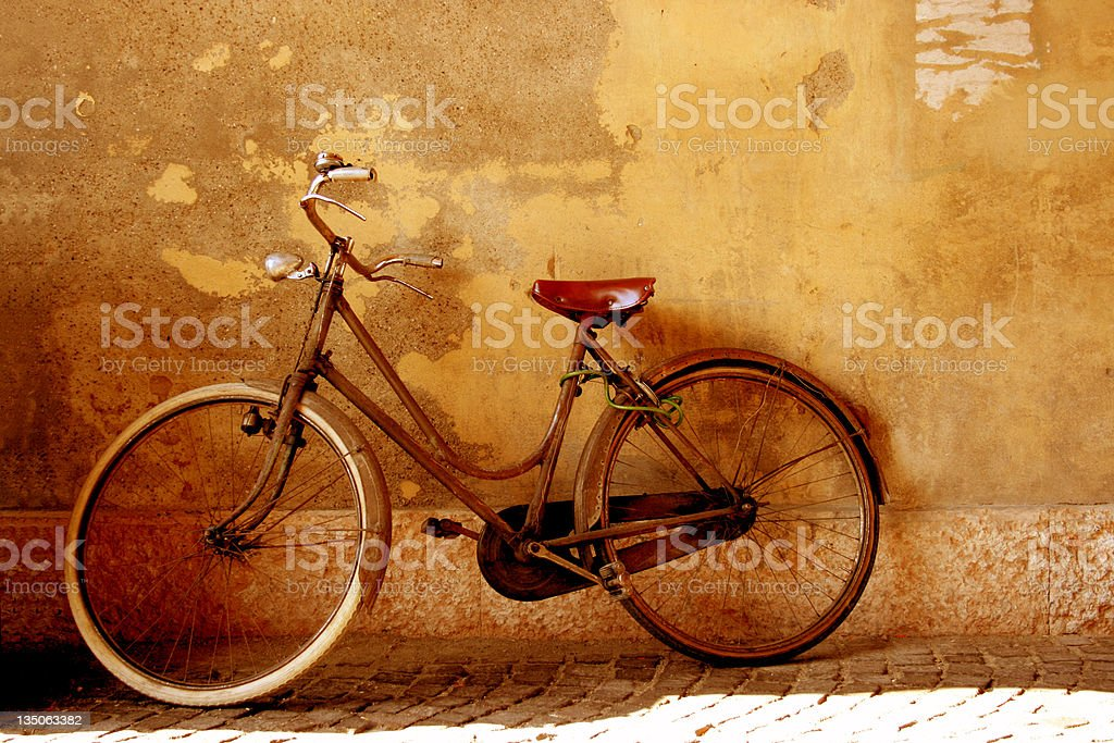 Vintage Bicycle Against Grunge Wall Sepia Toned royalty-free stock photo