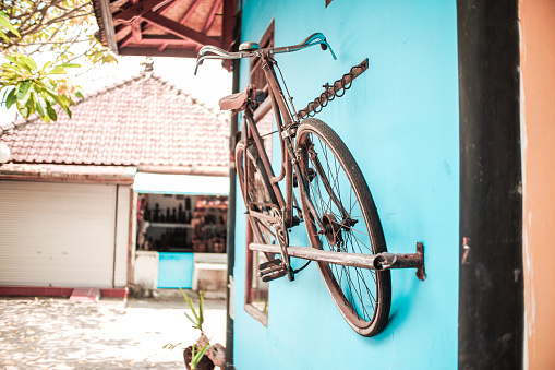 a vintage bicycle displayed on a blue wall to attract tourists