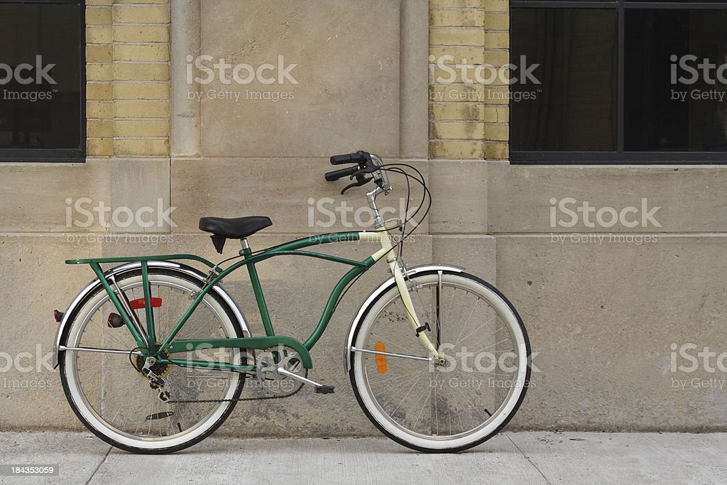 Vintage Bicycle Leaning Against Brick, Concrete Wall with Windows royalty-free stock photo