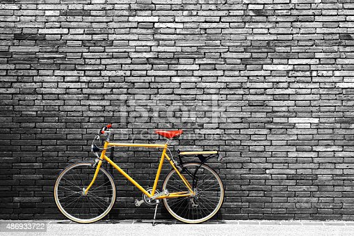 Vintage bicycle on roadside with black and white brick wall background