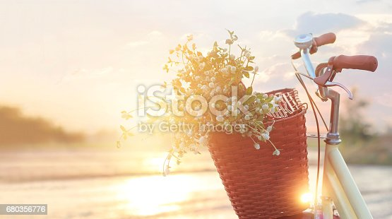 istock vintage bicycle with flowers in the basket on summer sunset rural background 680356776