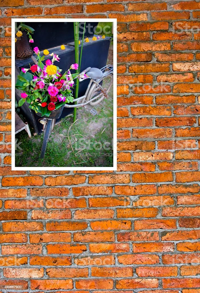 Vintage bicycle with flowers photo on brick wall. stock photo