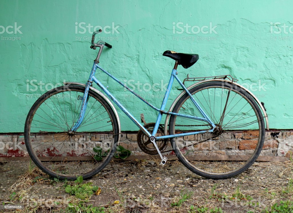 Vintage bicycle with green wall stock photo