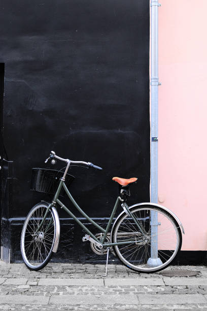 vintage bike leaning against a wall stock photo