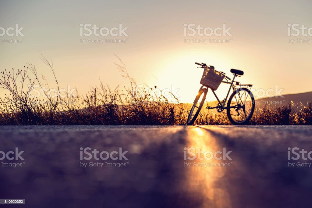 Vintage bike parked on country road at sunset. Copy space. stock photo