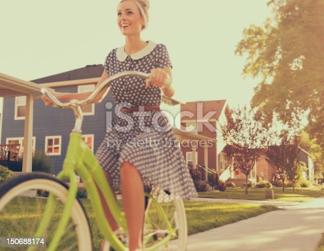 A retro female enjoys a ride on her vintage bike in the summer afternoon.