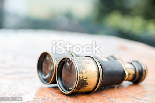 istock Vintage binoculars on wooden background 1041211938