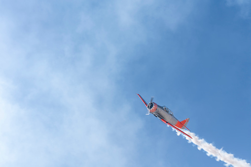 Vintage biplane does loop stunt with smoke trails. old airplane
