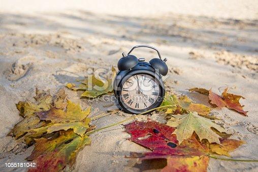 istock Vintage black alarm clock on autumn leaves. Time change abstract photo. 1055181042