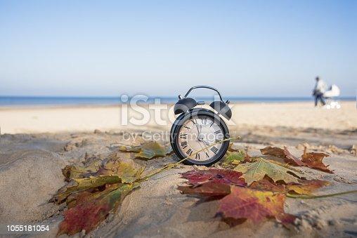 istock Vintage black alarm clock on autumn leaves. Time change abstract photo. 1055181054