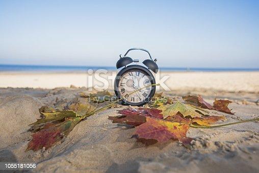 istock Vintage black alarm clock on autumn leaves. Time change abstract photo. 1055181056