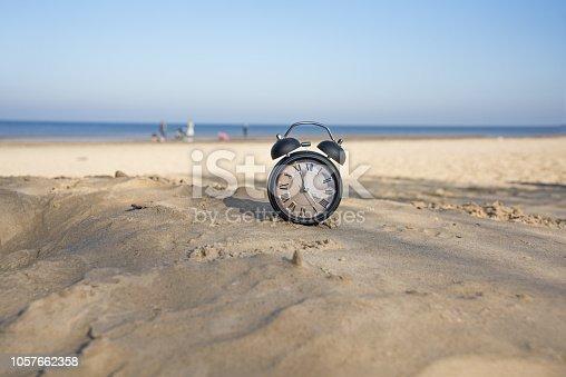 istock Vintage black alarm clock on autumn leaves. Time change abstract photo 1057662358