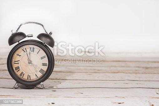 istock Vintage black alarm clock on autumn leaves. Time change abstract photo 1057662366