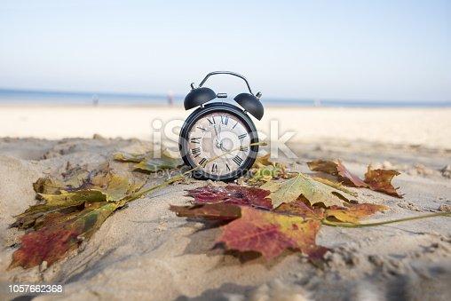 istock Vintage black alarm clock on autumn leaves. Time change abstract photo 1057662368