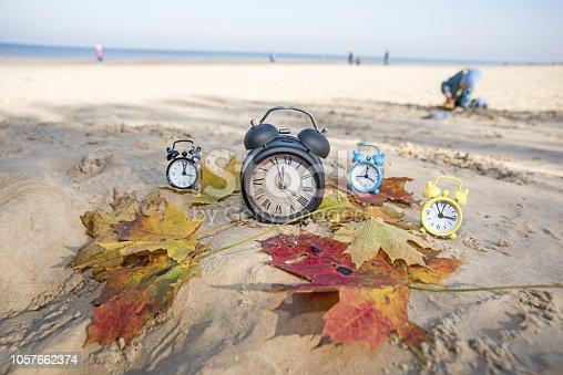 istock Vintage black alarm clock on autumn leaves. Time change abstract photo 1057662374