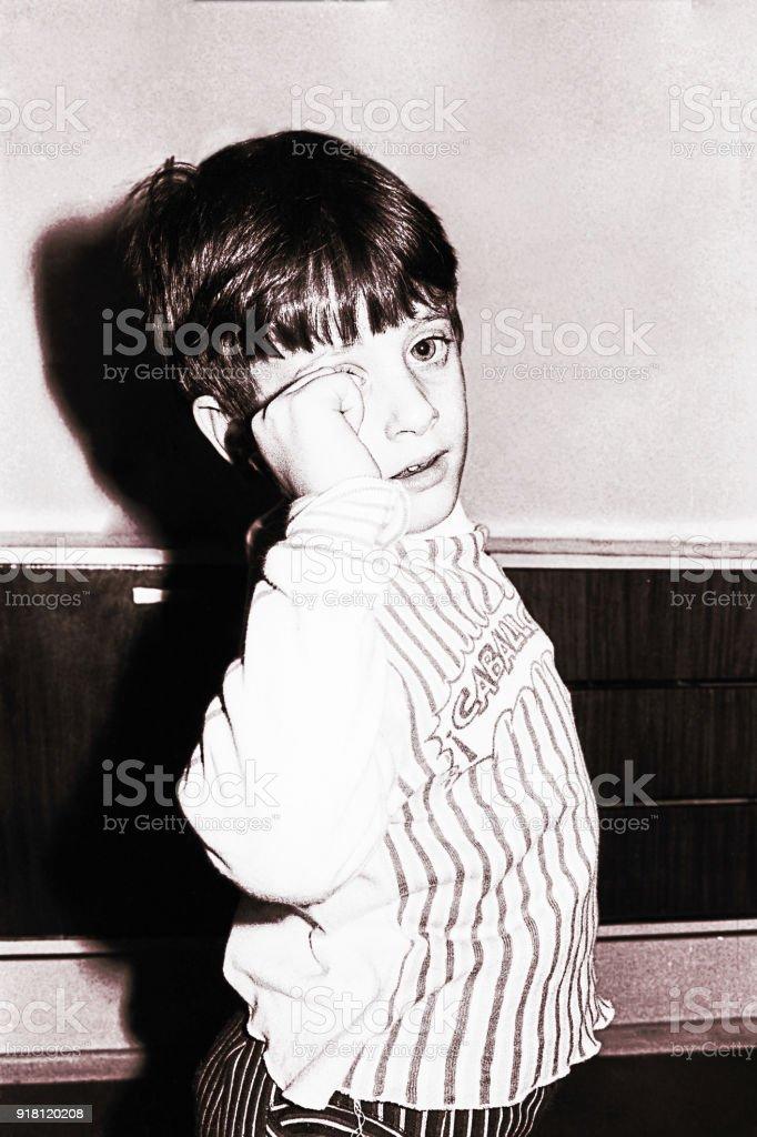 Vintage black and white boy rubbing his eyes stock photo