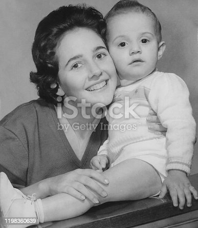 Vintage black and white image taken in 1960 of a caucasian Young woman posing with her one year old child boy