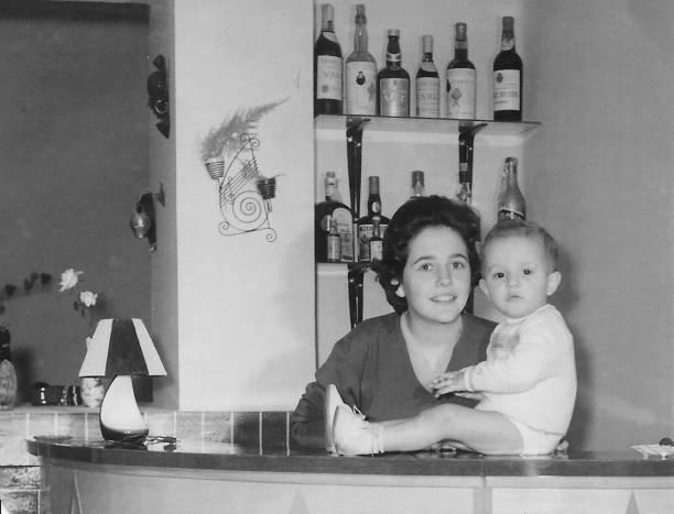 vintage czarno-białe zdjęcie zrobione w 1960 roku młoda kobieta pozowanie z jej rocznego chłopca dziecka - archiwalny zdjęcia i obrazy z banku zdjęć