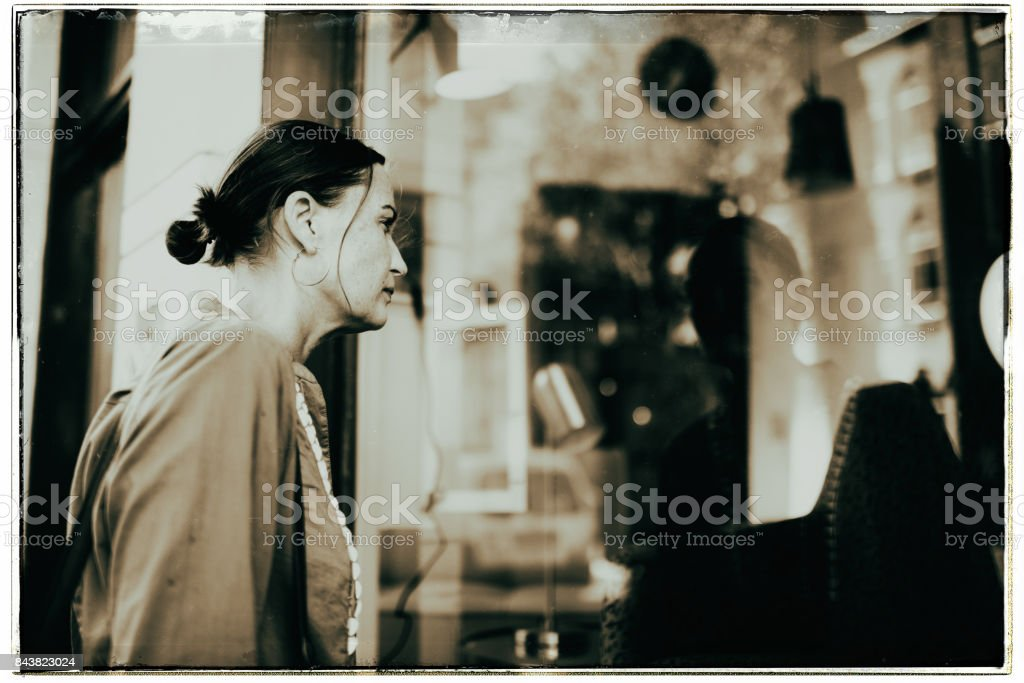 Vintage black and white photo of woman on street looking into storefront stock photo