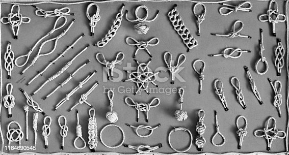 501889762istockphoto Vintage black and white wall background texture of navy nautical marine sailors binding knots. 1164690548