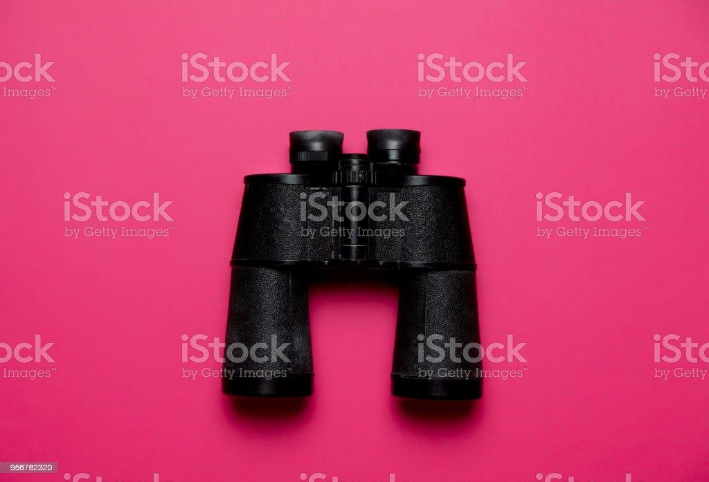 Vintage black binoculars on pink stock photo