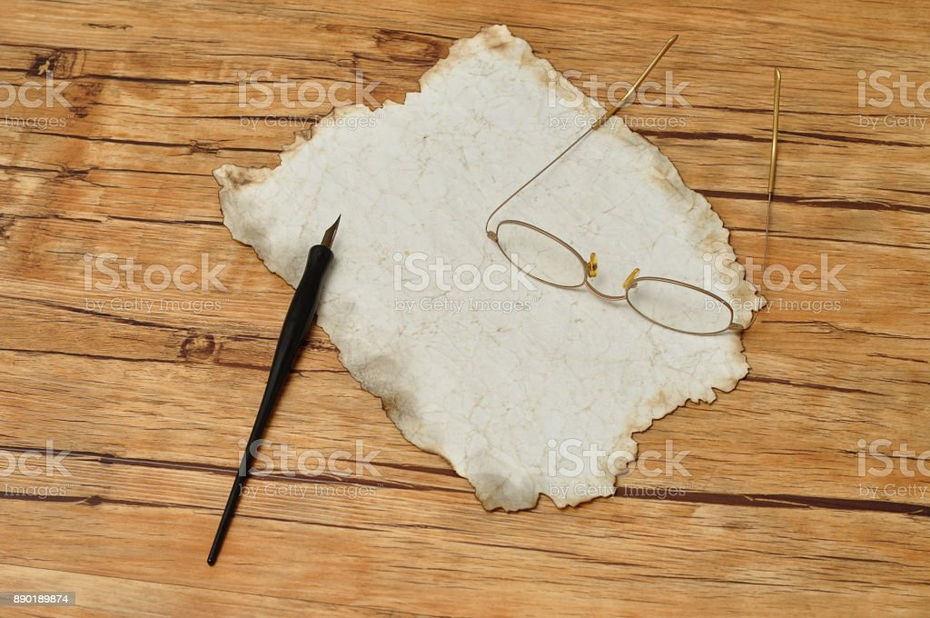 A vintage black fountain pen with old paper and reading glasses stock photo