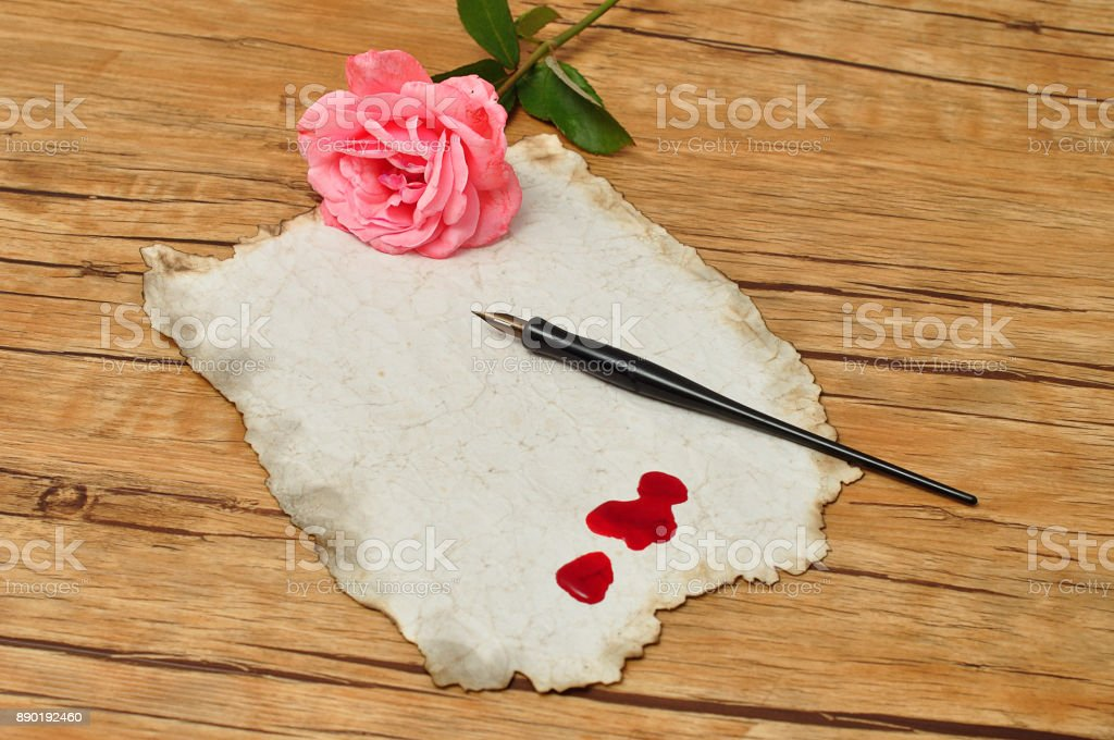 A vintage black fountain pen with old paper with drops of blood and a pink rose stock photo